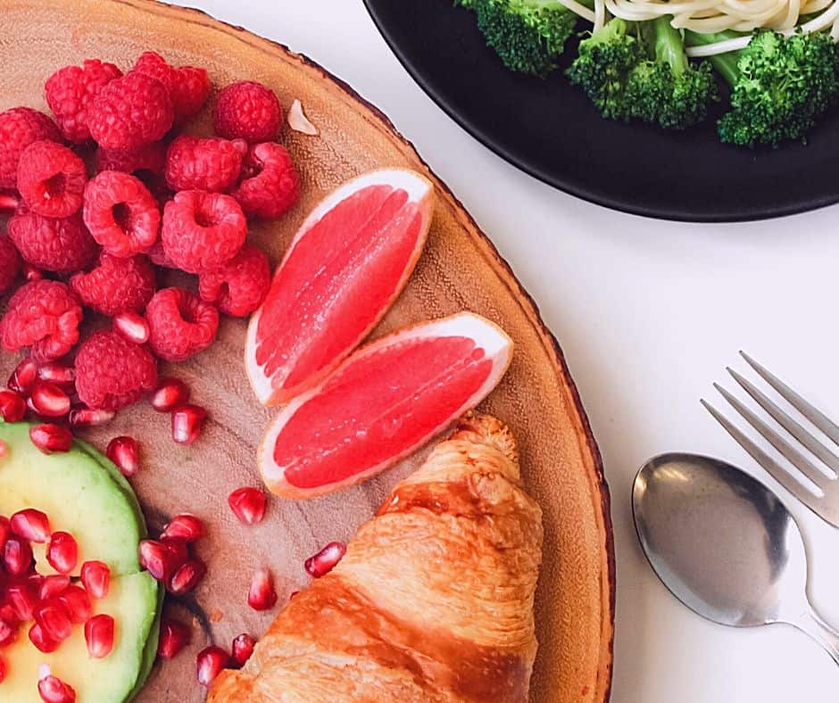 Croissant with avocado, berries and broccoli on platter that may tempt hunger