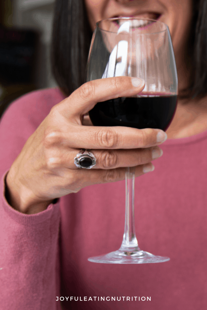 Tansy Boggon holding a glass of red wine