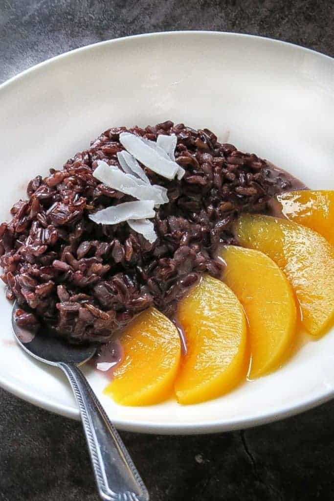Black Rice Pudding with Coconut Milk and Sliced Peaches in White Bowl