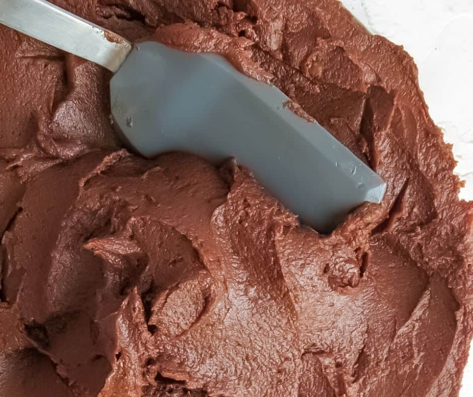 Spatula with carving into chocolate frosting