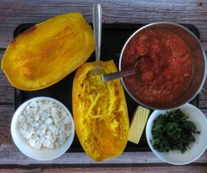 ingredients for Spaghetti Squash Lasgana Boats separated in bowls on black baking tray