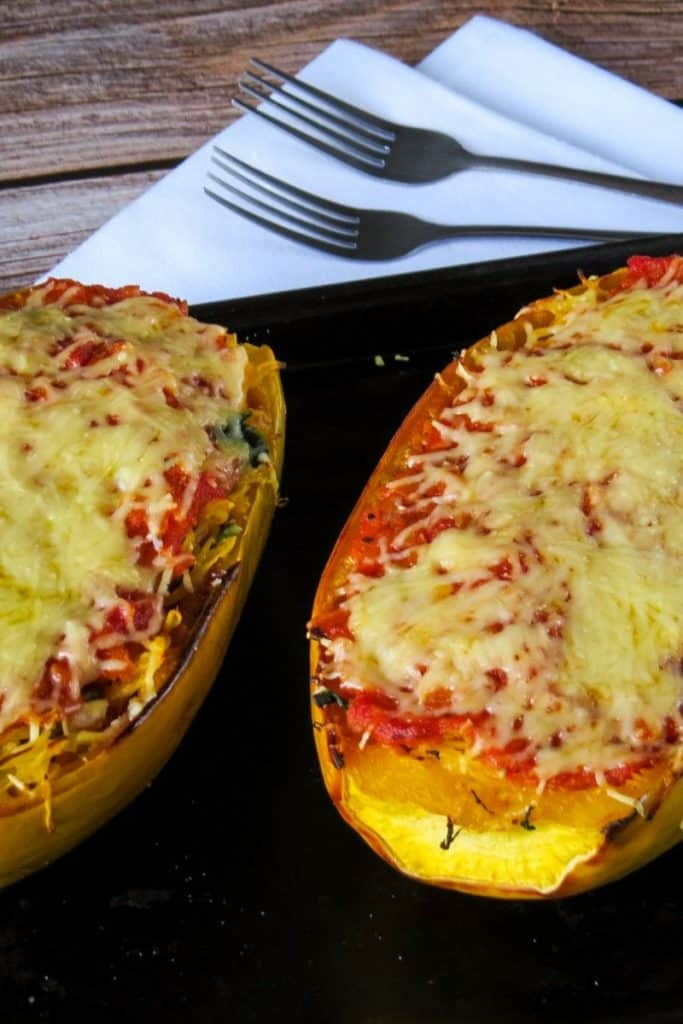 two Spaghetti Squash Lasgana Boats on black baking tray with fork in background