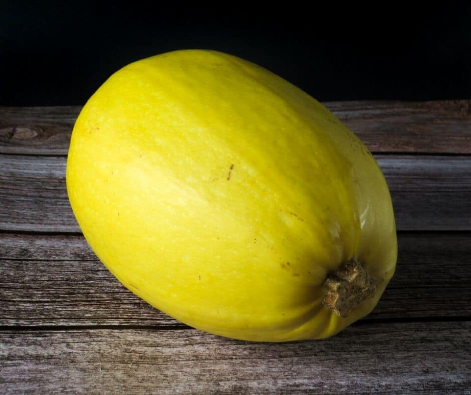 whole spaghetti squash on wooden surface