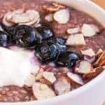 close up of bowl of steel cut oats porridge with blueberries, sliced almonds and yogurt