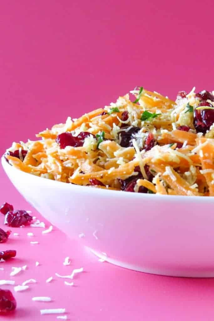 Coconut Carrot Salad in white bowl against pink background