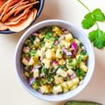 bowl pineapple salsa with corn chips and avocado