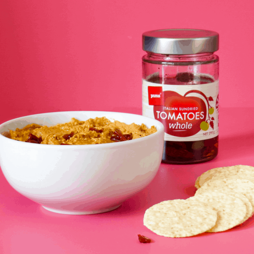 bowl of sundried tomato hummus with jar of sundried tomatos and brown rice crackers