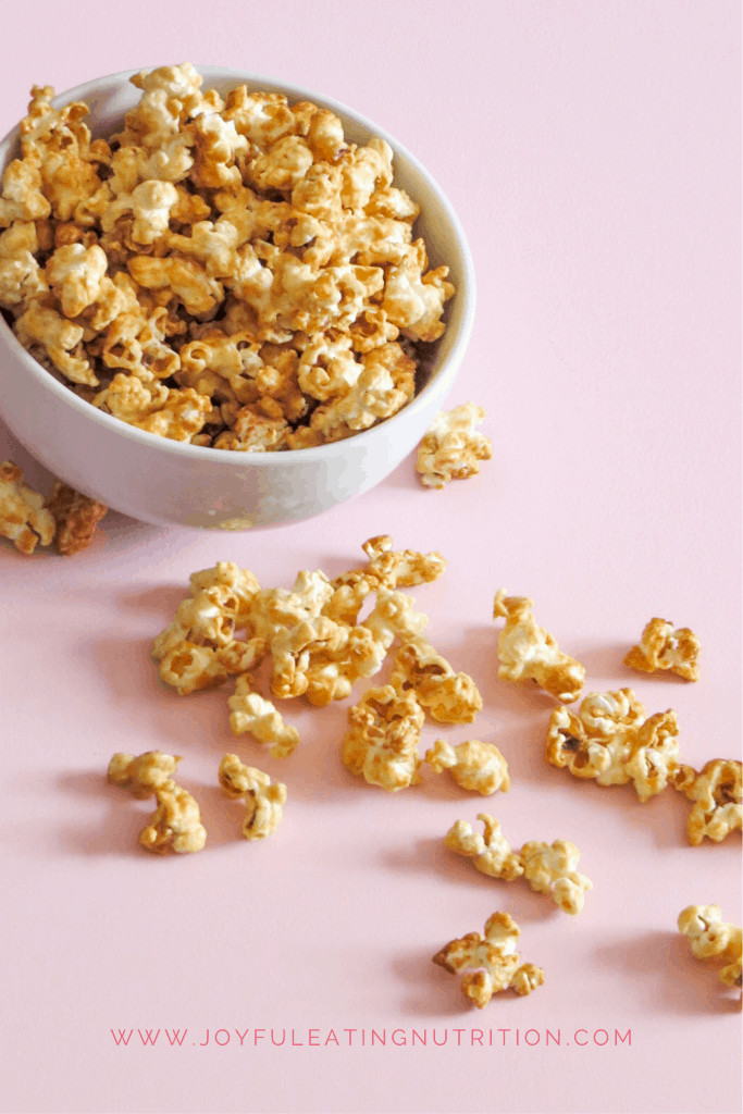 Caramel Popcorn tipped out of a white bowl on a pink surface