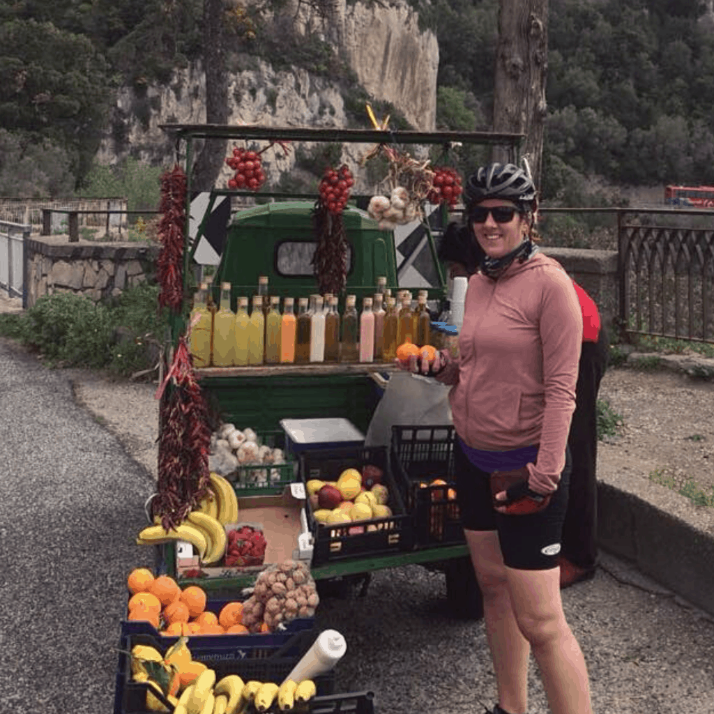 Tansy in cycling clothing by a food stand on the Amalfi Coast
